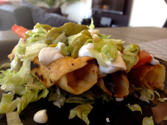 Taquitos Dorados with Lettuce, Mex Cream, Tomato, Onion and Salsa.