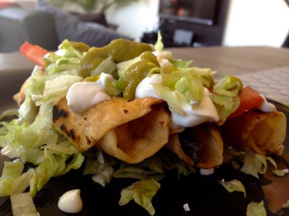 Taquitos Dorados with Lettuce, Mex Cream, Tomato, Onion and Salsa.